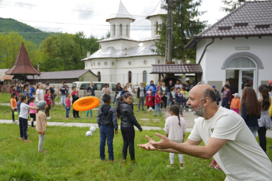 Valeriu Nicolae, the founder of the Casa Buna NGO, catches a frisbee thrown by a child during an eyesight examination performed by volunteer ophthalmologists, in Nucsoara, Romania, Saturday, May 29, 2021. (AP Photo/Vadim Ghirda)