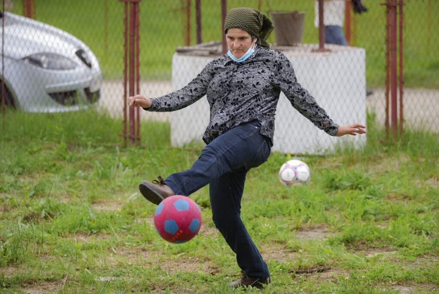 A woman kicks a ball after she took her children for an eyesight examination performed by volunteer ophthalmologists, in Nucsoara, Romania, Saturday, May 29.