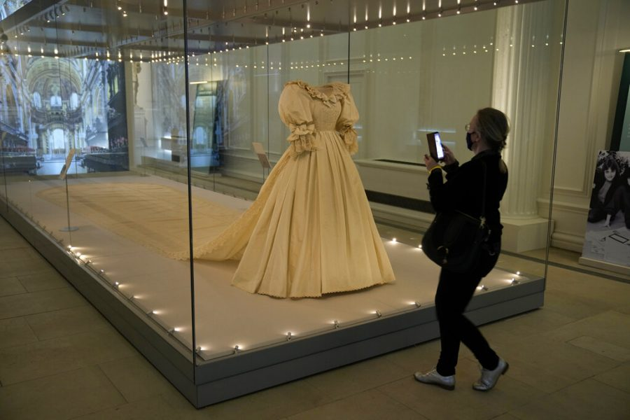 A journalist stands next to the wedding dress of Britain's Princess Diana during a media preview for the