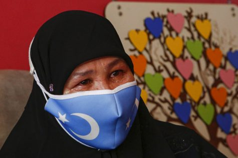 Bumeryem Rozi, a Uyghur quoted, wearing a blue face mask.