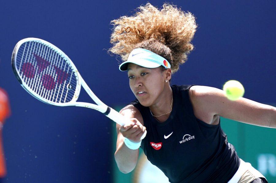 Naomi Osaka hitting a tennis ball with a racket.