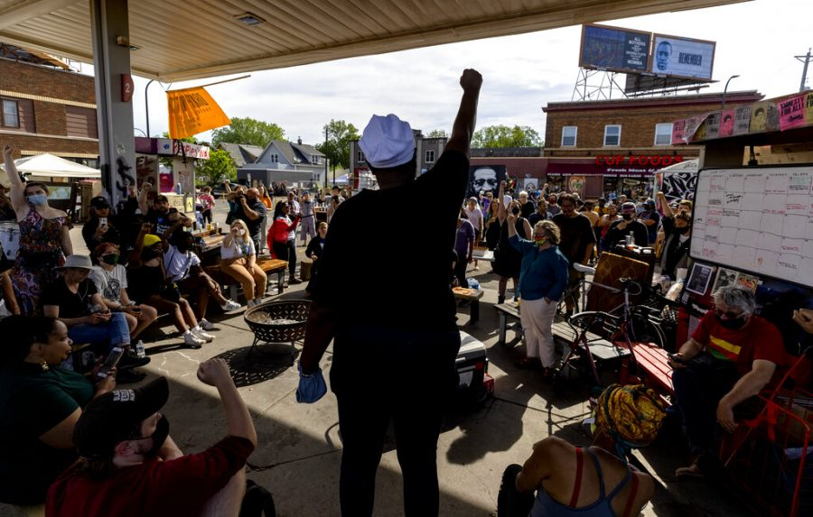 A crowd gathers near a gas station at George Floyd Square in Minneapolis on Thursday, June 3, 2021.  Crews have removed concrete barriers, artwork, flowers and other items from the intersection that has been a sprawling memorial to George Floyd since his death last year.  (Carlos Gonzalez /Star Tribune via AP)